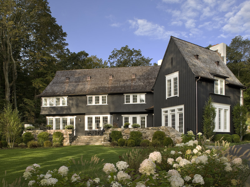 The rambling two-story house drew from English and Swedish country precedents, specifically details from the 18th century home of botanist Carl Linnaeus. Most of the façade is black-painted wood with trim, while one side is stark white stucco. Ike Kligerman Barkley